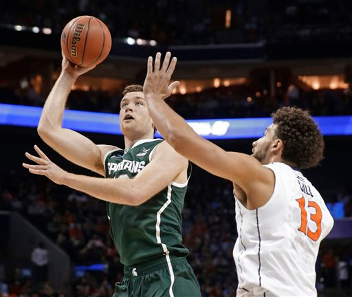 . Michigan State\'s Matt Costello, left, shoots over Virginia\'s Anthony Gill, right, during the first half of an NCAA tournament college basketball game in the Round of 32 in Charlotte, N.C., Sunday, March 22, 2015. (AP Photo/Gerald Herbert)