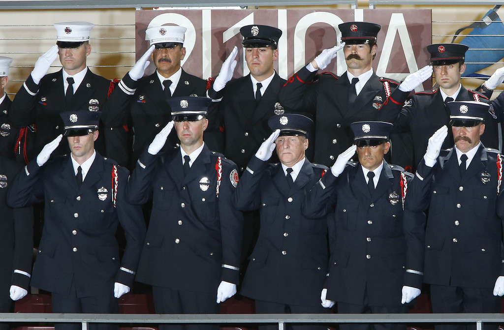 . Firefighters from Sacramento stand during the national anthem during a memorial service honoring 19 fallen firefighters at Tim\'s Toyota Center July 9, 2013 in Prescott Valley, Arizona.  (Photo by David Kadlubowski-Pool/Getty Images)