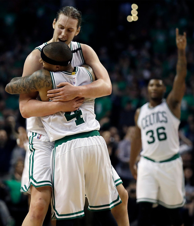 . Boston Celtics guards Isaiah Thomas (4) and Marcus Smart (36) celebrate with center Kelly Olynyk (41) after Olynyk sank a basket during the fourth quarter of Game 7 of a second-round NBA basketball playoff series against the Washington Wizards, Monday, May 15, 2017, in Boston. (AP Photo/Charles Krupa)