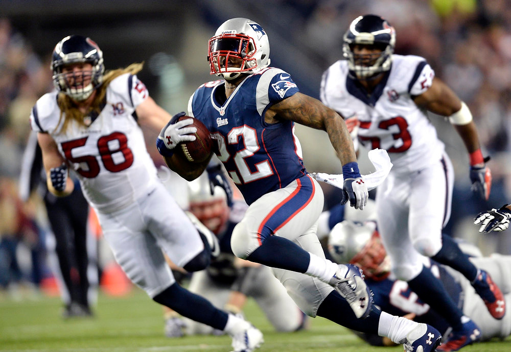 Description of . New England Patriots running back Stevan Ridley (22) runs for a first down during the fourth quarter of their NFL AFC Divisional playoff football game against the Houston Texans in Foxborough, Massachusetts January 13, 2013. At left is Texans\' Brooks Reed and at right Texans\' Bradie James.  REUTERS/Gretchen Ertl