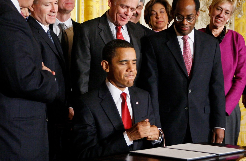 . President Barack Obama tugs on a tight pen cap after he signed an executive order establishing the Economic Recovery Advisory Board as its members look on, Friday, Feb. 6, 2009, in the East Room of the White House in Washington. (AP Photo/Charles Dharapak)