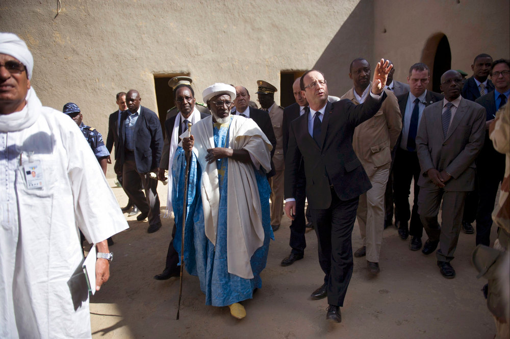 Description of . France\'s President Francois Hollande (R) walks ahead of Mali\'s interim president Dioncounda Traore (3rdR, partially hidden), as they visit the Grand Mosque in Timbuktu, during his one-day visit to Mali, February 2, 2013. French President Hollande flew to Mali on Saturday to support French troops fighting Islamist rebels in the Sahel nation and he visited the famed ancient city of Timbuktu that was recaptured from al Qaeda-allied fighters six days ago. REUTERS/Fred Dufour/Pool