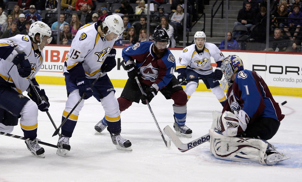 . Nashville Predators left wing Sergei Kostitsyn (74), left, of Belarus, scores against Colorado Avalanche goalie Semyon Varlamov (1), of Russia, as Predators center Craig Smith (15) and Avalanche defenseman Greg Zanon (4) join the play during the first period of an NHL hockey game, Monday, Feb. 18, 2013, in Denver. (AP Photo/Joe Mahoney)