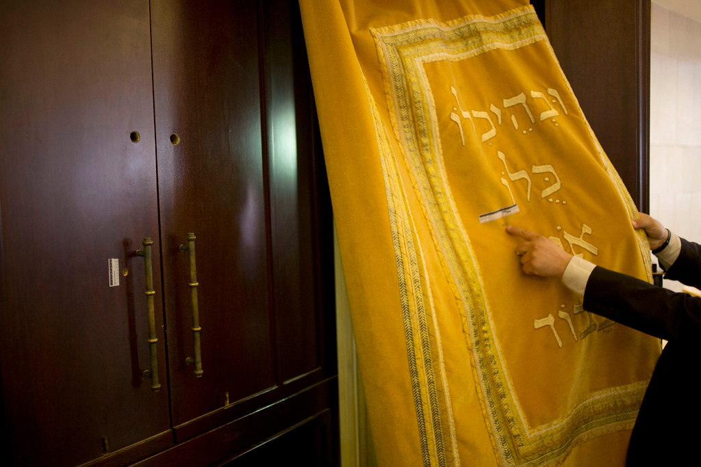 . A man shows bullet hole and forensic evidence inside the Synagogue after a shooting attack in Jerusalem, Tuesday, Nov. 18, 2014. Two Palestinians stormed a Jerusalem synagogue on Tuesday, attacking worshippers praying inside with knives, axes and guns, and killing four people before they were killed in a shootout with police, officials said. (AP Photo/Ariel Schalit)