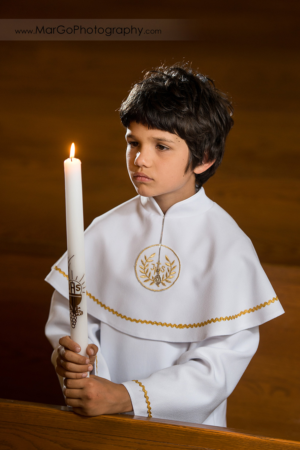 first communion boy in white alb holding candle in wooden San Jose church pews