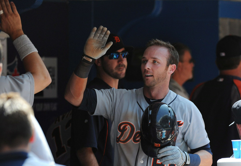 . Detroit Tigers\' Andrew Romine celebrates with teammates in the dugout after being driven home on a ground rule double by Ian Kinsler in the fourth inning against the Toronto Blue Jays  during a baseball game on Sunday, Aug. 10, 2014, in Toronto. (AP Photo/The Canadian Press, Jon Blacker)