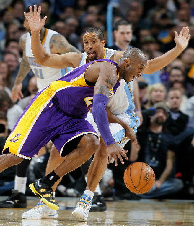 . Los Angeles Lakers guard Kobe Bryant, front, pursues a loose ball as Denver Nuggets guard Andre Miller  defends in the third quarter of the Nuggets\' 119-108 victory in an NBA basketball game in Denver on Monday, Feb. 25, 2013. (AP Photo/David Zalubowski)