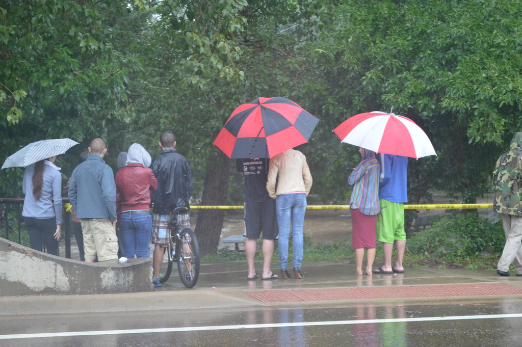 . People watching the Boulder Creek flood after the siren alerted to imminent flood waters heading that way. Photo by Natalie Boyd