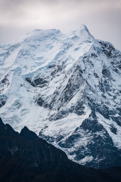 A snow-capped peak stands out against a white sky