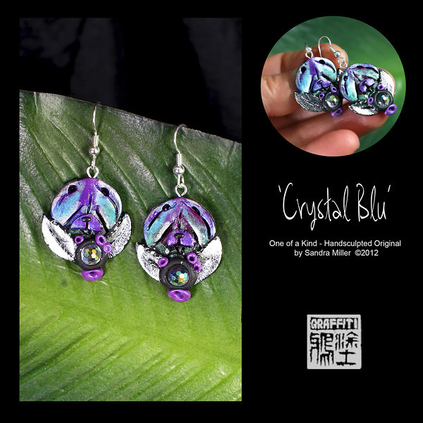 """CRYSTAL BLU This fun set of Chow earrings started with my creating an iridescent and metallic panel of blue/purple and silver, then sculpting the earrings from the """"sweet spots"""" in the washes of color.  The silver leaves frame the head perfectly with teeny purple flower buds as well.  Each earring features a 1920's crystal cabochon which is like a mini disco ball  they have so many facets and auraborealis coloration.  The photo simply can't show off the fire in these earrings!  EARRINGS MEASURE 1 """" long x 3/4"""" wide without wire"""