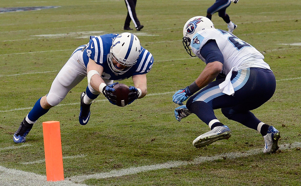 . Indianapolis Colts tight end Jack Doyle (84) dives past Tennessee Titans safety George Wilson, right, into the end zone to score a touchdown on a 1-yard pass play in the first half of an NFL football game Sunday, Dec. 28, 2014, in Nashville, Tenn. (AP Photo/Mark Zaleski)