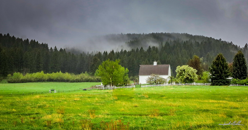 Classic white barn in the rising mist