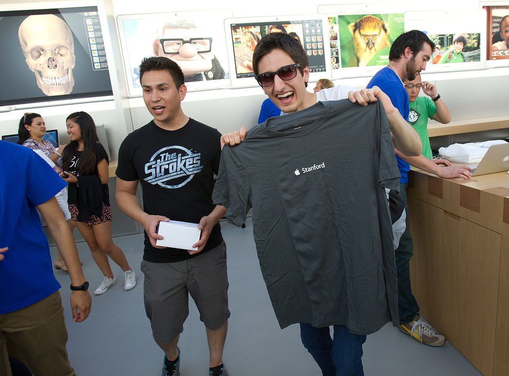 . Mark Sagherian, right, shows off  the free Apple T-Shirt he received at the redesigned Apple Store at the Stanford Shopping Center in Palo Alto, Calif., on Saturday, Sept. 7, 2013.  At left is Luis Carrasco. (LiPo Ching/Bay Area News Group)