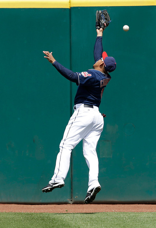 . Cleveland Indians\' Ezequiel Carrera jumps for a double hit by Minnesota Twins\' Josh Willingham in the first inning. (AP Photo/Tony Dejak)