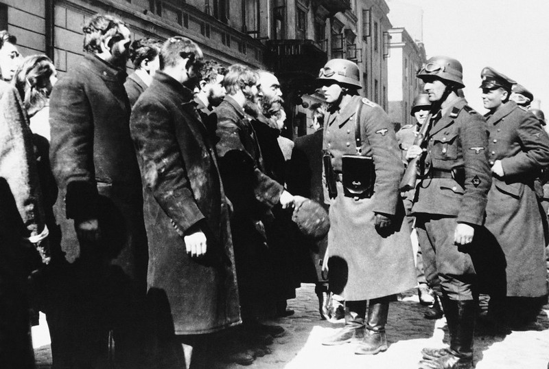 . Nazi officers talk with citizens of the Warsaw ghetto, Poland, spring 1943.  (AP Photo)