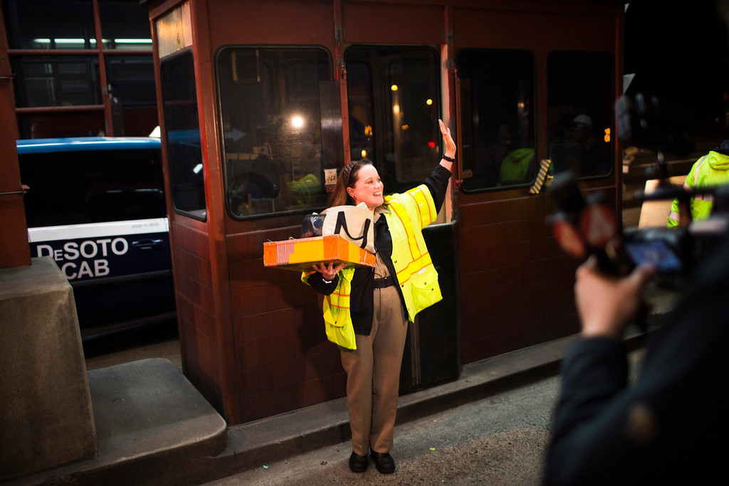 . Toll collector Marilyn Alvardo (C) waves as she leaves her tollbooth, as the last human toll collector, at the Golden Gate Bridge toll plaza in San Francisco, California March 27, 2013. The Golden Gate Bridge will convert from manned tollbooths to a full electronic tolling system starting today. With the automated system in place, motorists will have the option of using the existing FasTrak electronic toll collection system or the newly implemented pay-by-plate option, according to the Golden Gate Bridge management. REUTERS/Stephen Lam
