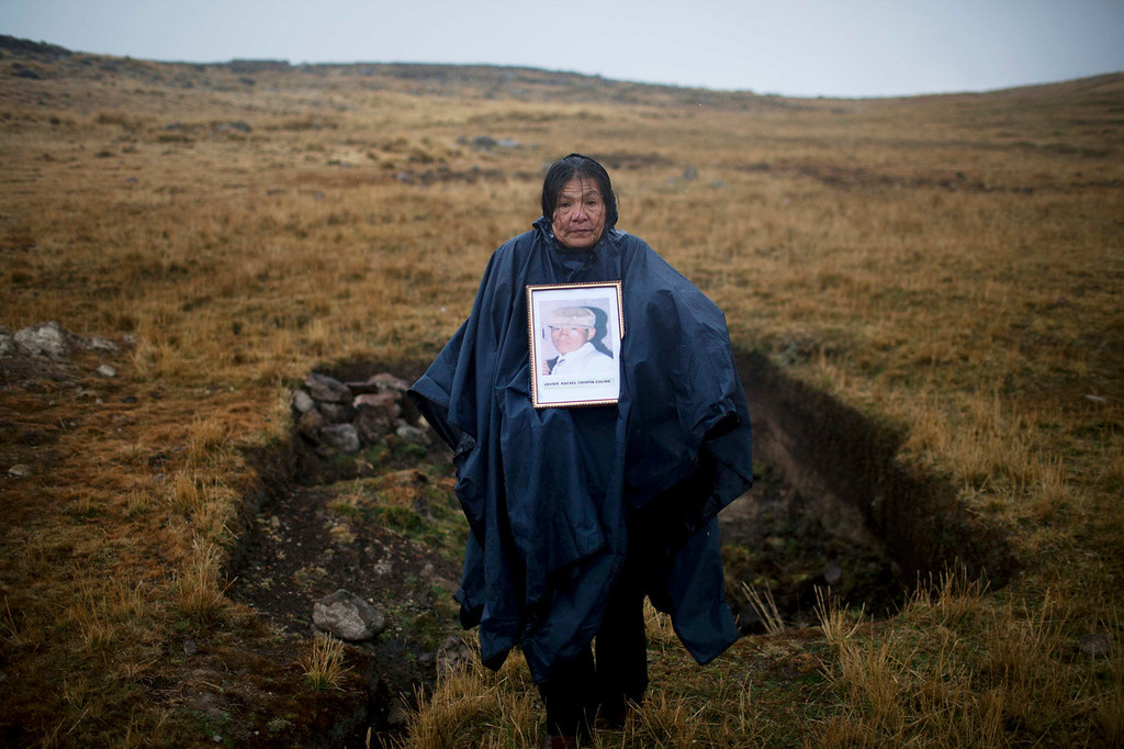 . Alicia Isabel Colina, 61, poses for a photo holding a portrait of her disappeared son, Javier Crispin Colina, in front of mass grave number 70, discovered by Colina and her husband, in Huancavelica, Peru. For almost a quarter century Colina and her husband scoured the mountains of Peru\'s poorest region in search of the son hauled away by soldiers from a friend\'s house in the middle of the night. Completely on their own, the couple found a total of 70 clandestine burial sites and unearthed three dozen bodies. (AP Photo/Rodrigo Abd)