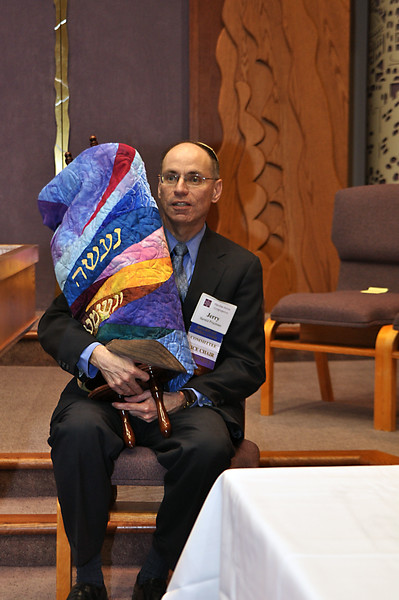 Jerry Friedman holds the new torah scroll, dressed for the first time in its new mantle (photo by Sam Backman)
