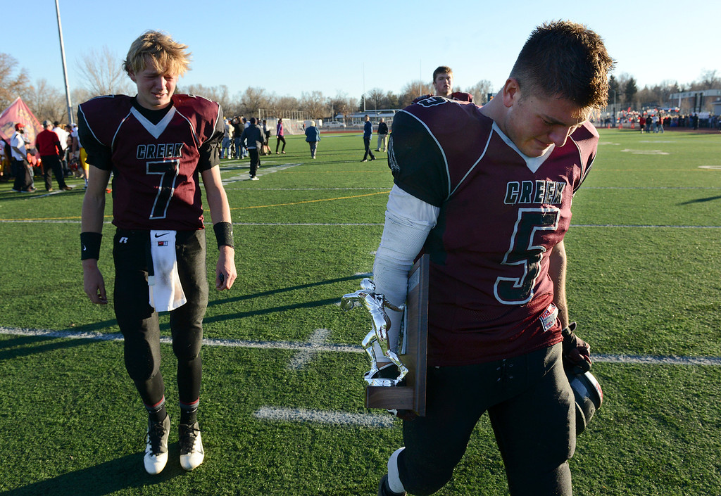 . Silver Creek captains Ben Sjobakken, left, and Andre Apodaca carry the second place trophy back to their team after losing the Class 3A state championship game to Coronado Saturday Nov. 30, 2013, by a score of 28-24, at Everly-Montgomery Field.  (Lewis Geyer/Times-Call)