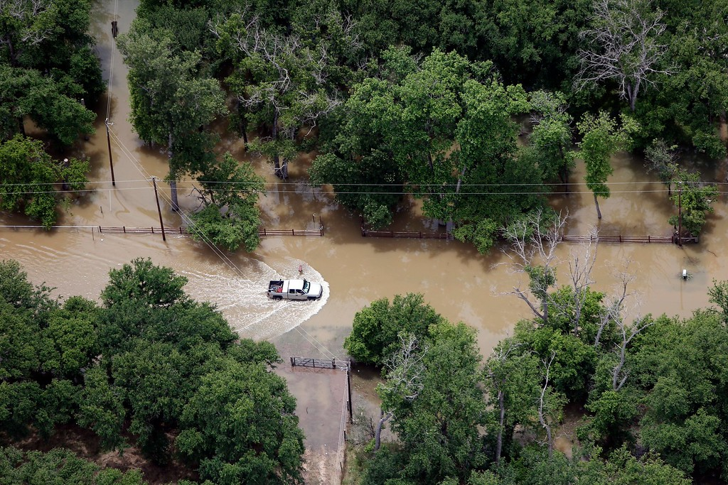 . A motorist drives through flood waters from the Brazos River in the Horseshoe Bend neighborhood, Friday, May 29, 2015, in Weatherford, Texas. Floodwaters submerged Texas highways and threatened more homes Friday after another round of heavy rain added to the damage inflicted by storms. (AP Photo/Brandon Wade)