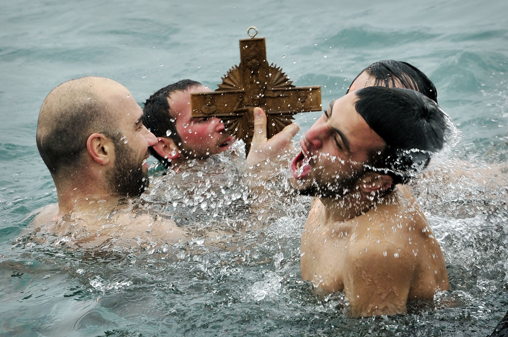 . A man hold a wooden cross he retrieved from the sea during a ceremony of the blessing of the waters marking the orthodox Epiphany Day at the port of Aegina island near Athens on January 6, 2014.  LOUISA GOULIAMAKI/AFP/Getty Images