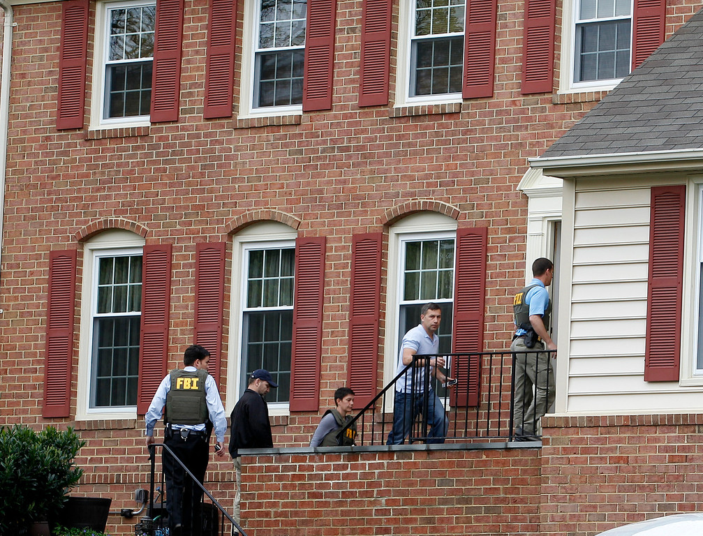 . FBI agents escort Ruslan Tsarni, uncle of the Boston Marathon bombing suspects, second from right, into his home in Montgomery Village in Md. Friday, April, 19, 2013. The brothers, who came from a Russian region near Chechnya, lived together on Norfolk Street in Cambridge, Mass. They had been in the country for about a decade, according to an uncle, Ruslan Tsarni of Montgomery Village, Md. (AP Photo/Jose Luis Magana)