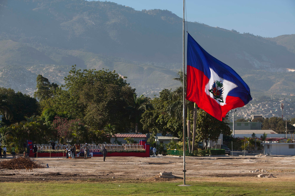 Description of . A Haitian national flag flies at half-mast on the front lawn of the former National Palace, marking the 3rd anniversary of the devastating 7.0 magnitude earthquake,  in Port-au-Prince, Haiti, Saturday, Jan. 12, 2013. Clad in black, several dozen senior government officials gathered where the elegant white palace had stood before it collapsed in the temblor and was later demolished. Most of the rubble created by the quake has since been carted away but more than 350,000 people still live in grim displacement camps. (AP Photo/Dieu Nalio Chery)