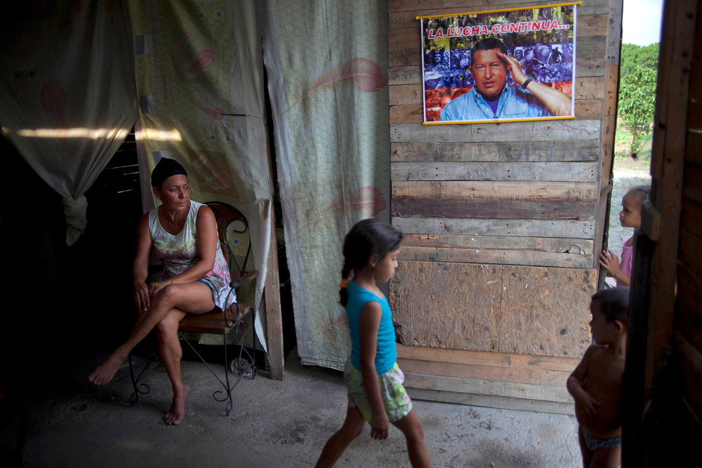 ". In this April 8, 2013 photo, Yadaira Nunez, 43, sits in her wooden shack next to a poster of Venezuela\'s late President Hugo Chavez that reads in Spanish; ""The battle continues...,\"" at a squatter settlement near Tacarigua, Venezuela. Outside Venezuela\'s capital, power outages, food shortages and unfinished projects abound; important factors heading into Sunday\'s election to replace Chavez, who died last month after a long battle with cancer. An estimated 2 million of Venezuela\'s country\'s nearly 30 million people lack permanent homes, and one of Chavez\'s anti-poverty \""missions\"" builds them. But it\'s been slow going. The government says it has built 370,500 homes and apartments over the past two years, and more than 3 million people applied for them. (AP Photo/Ramon Espinosa)"