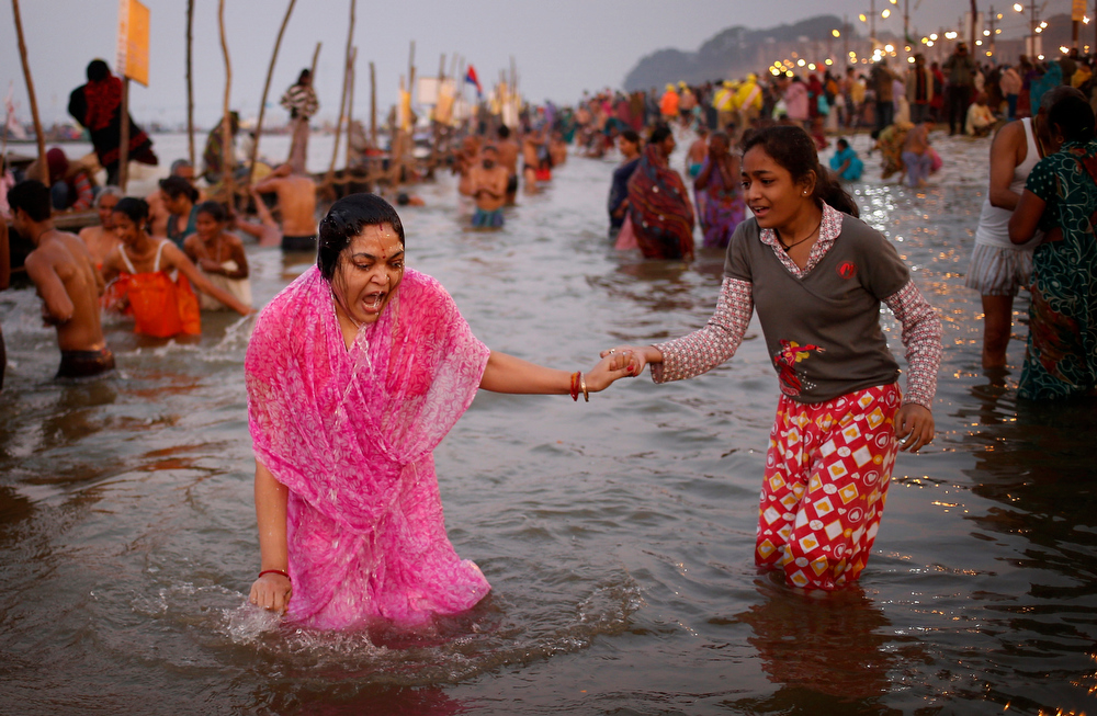 Description of . A Hindu devotee gasps after a dip in the cold water at