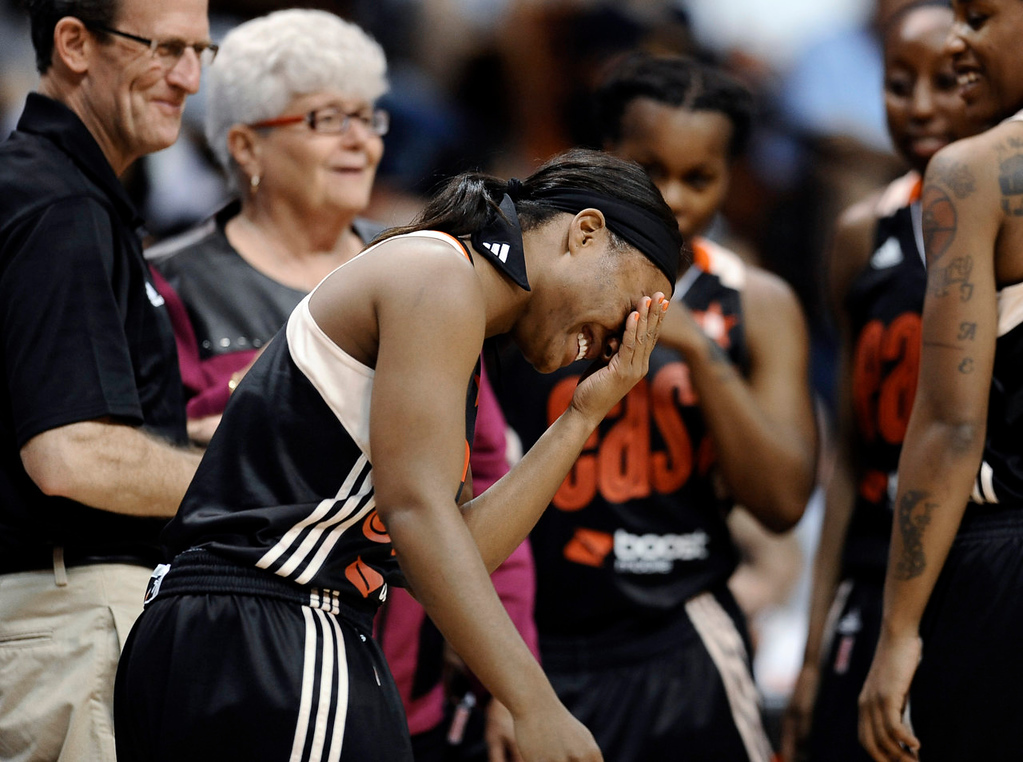 . East\'s Ivory Latta, of the Washington Mystics, laughs after receiving a check-up from a trainer after being fouled during the first half. (AP Photo/Jessica Hill)