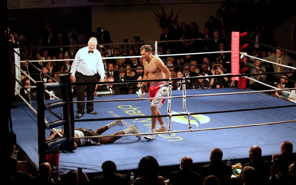 ". Mitt Romney stands over  Evander Holyfield after knocking him down during a fight  in a charity boxing event on May 15, 2015 in Salt Lake City, Utah. The event was held to raise money for  ""Charity Vision\"" a charity that aims to restore sight to the blind and visually impaired. (Photo by George Frey/Getty Images)"