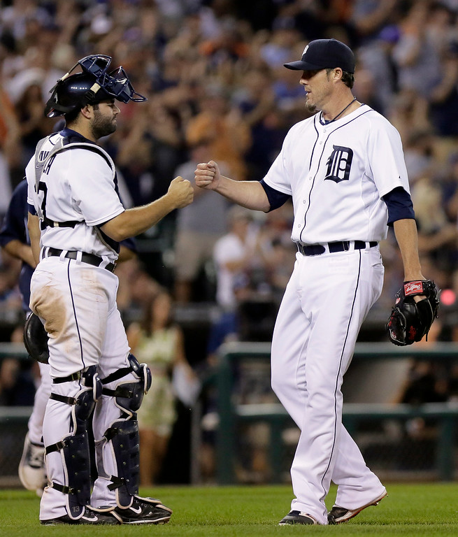 . Detroit Tigers pitcher Joe Nathan, right, receives a fist-bump from catcher Alex Avila after recording his 25th save in a 4-2 win over the Seattle Mariners in a baseball game Saturday, Aug. 16, 2014, in Detroit. (AP Photo/Duane Burleson)