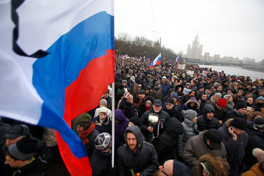 ". People with Russian national flags march in memory of opposition leader Boris Nemtsov who was gunned down on Friday, near the Kremlin, with the Kremlin in the background in Moscow, Russia, Sunday, March 1, 2015. Thousands converged Sunday in central Moscow to mourn veteran liberal politician Boris Nemtsov, whose killing on the streets of the capital has shaken Russia\'s beleaguered opposition. They carried flowers, portraits and white signs that said ""I am not afraid.\"" (AP Photo/Denis Tyrin)"