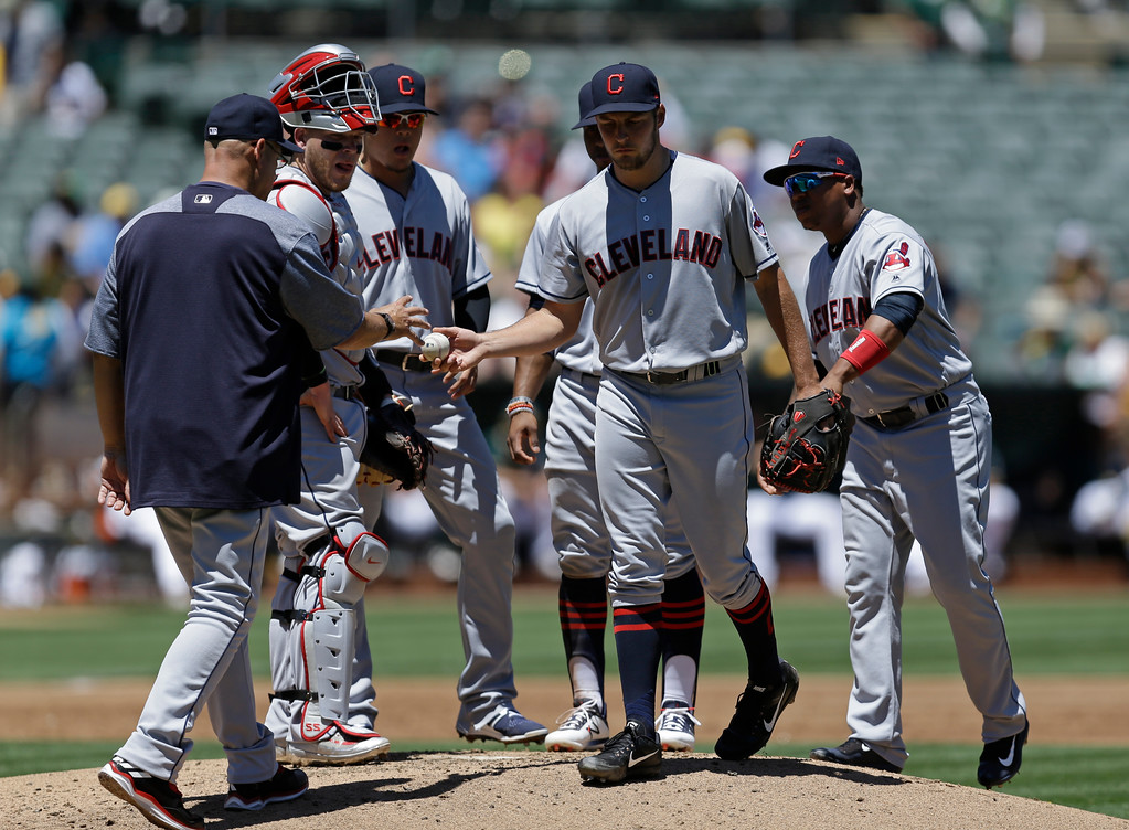 . Cleveland Indians\' Trevor Bauer, center, hands the ball to manager Terry Francona, left, as he is removed in the first inning of a baseball game against the Oakland Athletics, Sunday, July 16, 2017, in Oakland, Calif. (AP Photo/Ben Margot)