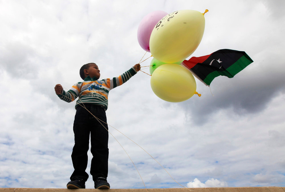Description of . A boy holds balloons with a Libyan flag, ahead of the second anniversary of the February 17 uprising, in Benghazi, February 16, 2013. The actual anniversary of the start of the revolt is not until Sunday, but celebrations began on Friday in remembrance of the arrest of a human rights lawyer that kindled the unrest. Cars flying national flags and blasting national songs honked their way through heavy traffic towards the courthouse, where about 2,000 were gathered, chanting anti-government slogans in between celebratory songs and speeches. REUTERS/Esam Al-Fetori