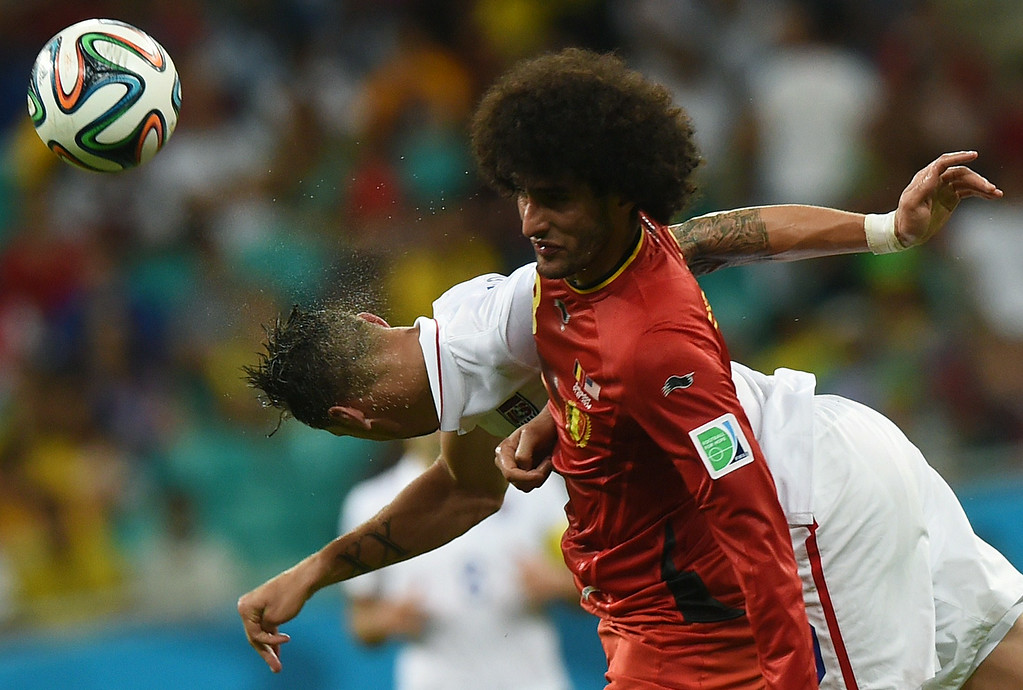 . US defender Geoff Cameron (L) heads the ball past Belgium\'s midfielder Axel Witsel during a Round of 16 football match between Belgium and USA at Fonte Nova Arena in Salvador during the 2014 FIFA World Cup on July 1, 2014.      AFP PHOTO/ FRANCISCO  LEONG/AFP/Getty Images