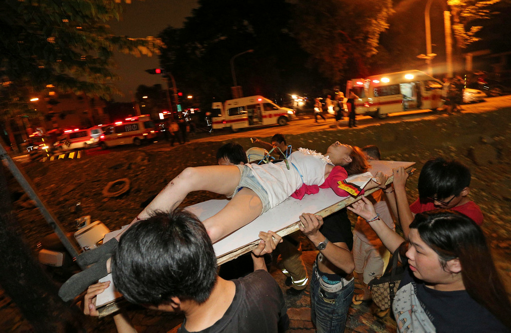 . A victim in a gas explosion from an underground gas leak is carried from the rubble in a main street in Kaohsiung, Taiwan, early Friday, Aug. 1, 2014.  A massive gas leakage early Friday caused five explosions that killed several people and injured over 200 in the southern Taiwan port city of Kaohsiung. (AP Photo)