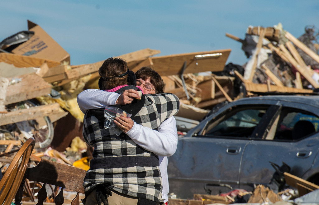 . Kim Bendixen, facing, is embraced by a friend as the toll of the day wears on as homeowners dig out what they can in Washington, Ill., Tuesday, Nov. 19, 2013, after more than 1,000 homes were devastated by a F4 tornado that passed through Sunday. Kim said that her father was rescued out of the rubble, and was doing better. The twister was the most powerful to hit Illinois since 1885 with wind speeds greater than 200 mph. (AP Photo/Journal Star, Fred Zwicky)