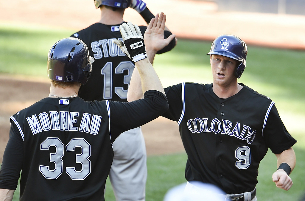 . SAN DIEGO, CA - AUGUST 13:  DJ LeMahieu #9 of the Colorado Rockies, right, is congratulated by Justin Morneau #33 after scoring during the third inning of a baseball game against the San Diego Padres at Petco Park on August 13, 2014 in San Diego, California.  (Photo by Denis Poroy/Getty Images)
