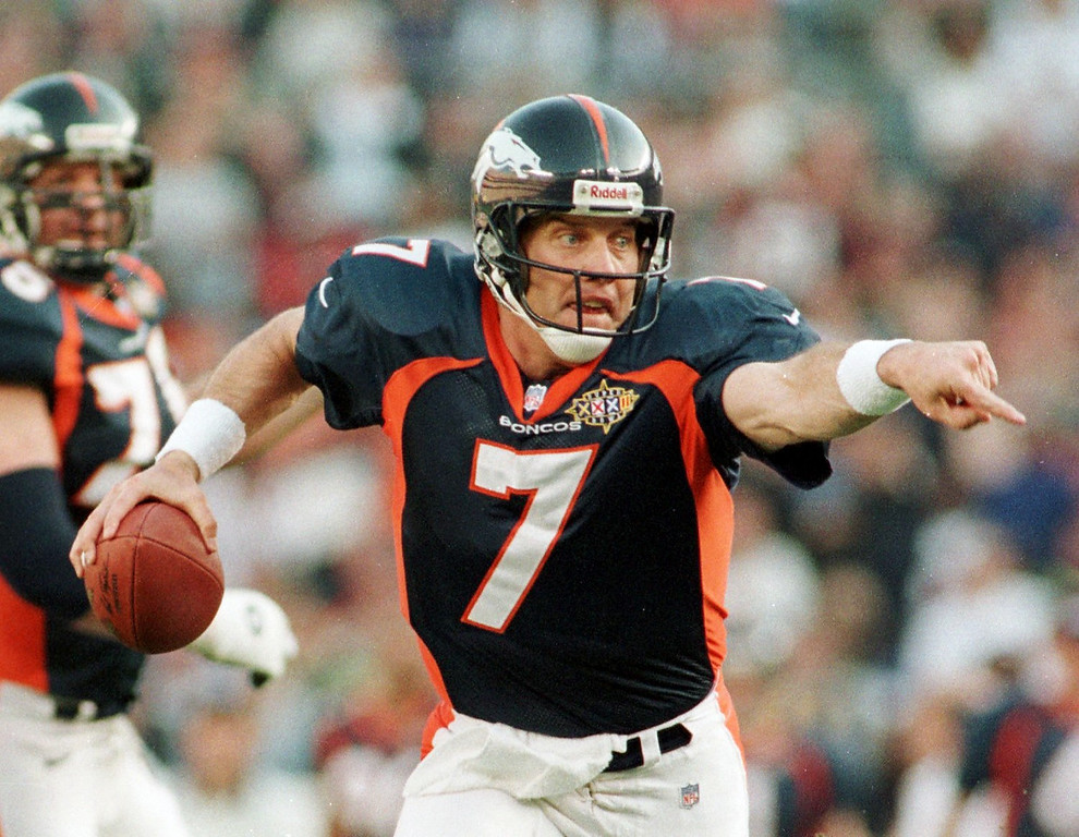 . Caption: Denver Broncos John Elway directs his blockers as he  scrambles for yardage during the first half of Super Bowl XXXII  in San Diego CA. The Broncos Faced the Green Bay Packers.  (Andy Cross/The Denver Post)