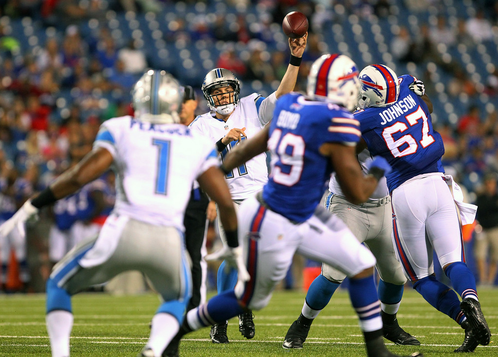 . Detroit Lions quarterback Kellen Moore, center, aims a pass at wide receiver Andrew Peacock (1) during the second half of a preseason NFL football game against the Buffalo Bills, Thursday, Aug. 28, 2014, in Orchard Park, N.Y. (AP Photo/Bill Wippert)
