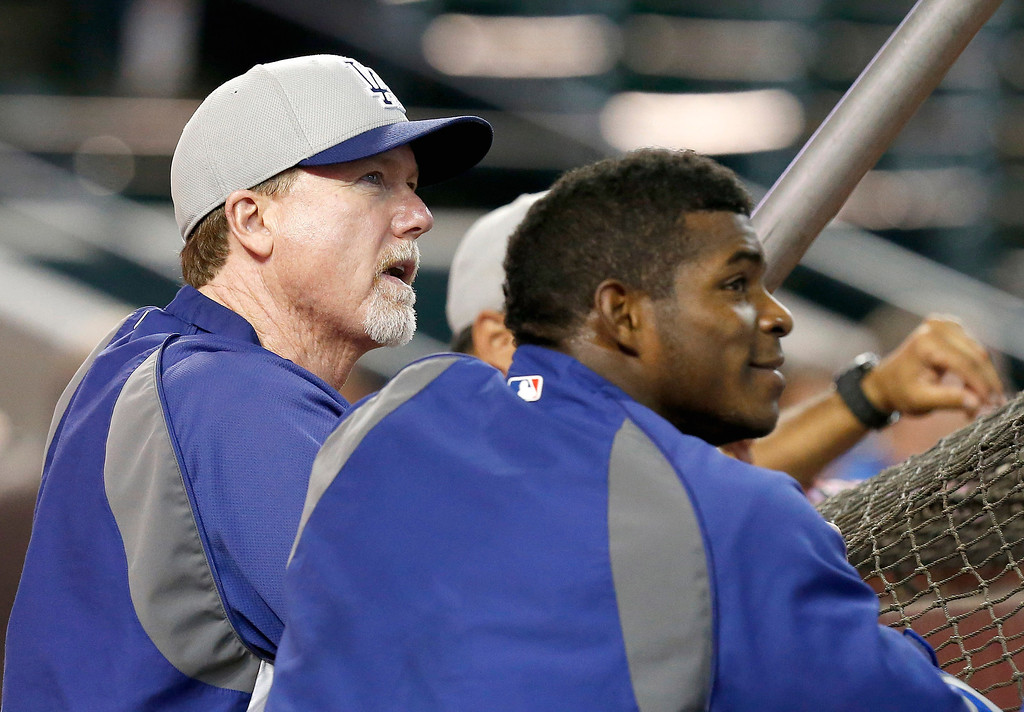 . Los Angeles Dodgers hitting coach Mark McGwire, left, talks with Yasiel Puig prior to a baseball game against the Arizona Diamondbacks on Monday, Sept. 16, 2013, in Phoenix. (AP Photo/Ross D. Franklin)