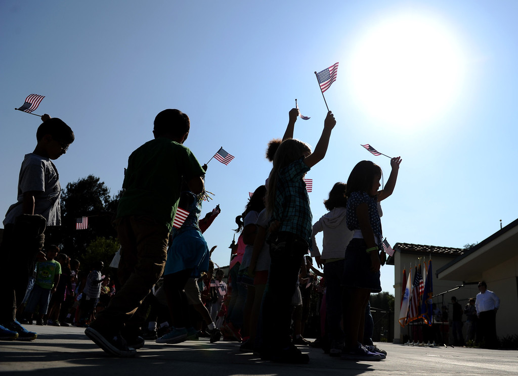 . (John Valenzuela/Staff Photographer) Students from Mission Elementary School in Redlands, wave American Flags during the schools Patriot�s Day celebration, marking the 12th Anniversary of the 9/11 attacks, Wednesday, September 11, 2013. Military veteran Robert Kafader discussed the tragic events that happen on Sept. 11, 2001, when nearly 3000 people were killed during the terrorist attacks 12 years ago.