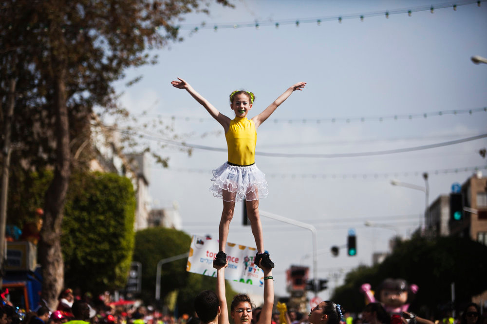 . A girl, dressed in a costume, performs during the annual parade for the Jewish holiday of Purim, in the Israeli city of Holon, near Tel Aviv February 24, 2013. Purim is a celebration of the Jews\' salvation from genocide in ancient Persia, as recounted in the Book of Esther. REUTERS/Nir Elias