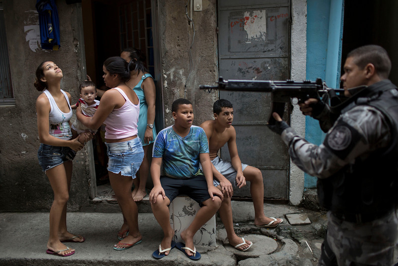 """. A military police officer patrols in front of residents during an occupation operation in the Mare slum complex, ahead of its \""""pacification,\"""" in Rio de Janeiro, Brazil, Tuesday, March 25, 2014. (AP Photo/Felipe Dana)"""