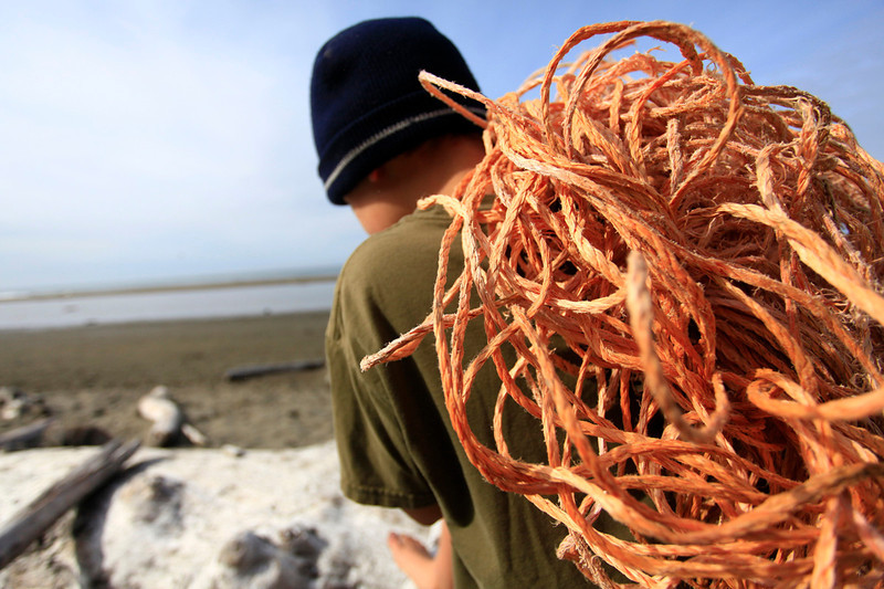 Little boy clears plastic rope from an Oregon beach.