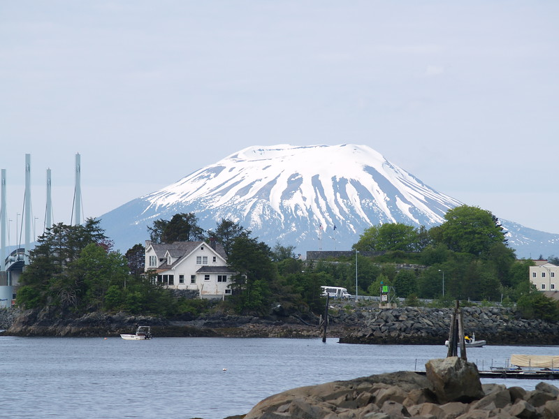 Mt. Edgecumbe, an exstinct cone volcano, is located on Kruzof Island, only 14 miles from Sitka. It provides a dramatic backdrop to the town. In the foreground are the support for the bridge to Japonski Island and the house of the publisher of the local paper. This photograph was taken in late May, 2007. The snow had melted up to the cone by the end of June.