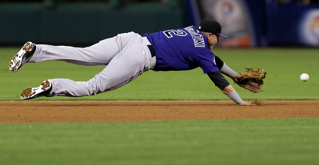 . Colorado Rockies\' Troy Tulowitzki lunges for a base hit by Philadelphia Phillies\' Domonic Brown in the fourth inning of a baseball game, Monday, Aug. 19, 2013, in Philadelphia. (AP Photo/Laurence Kesterson)