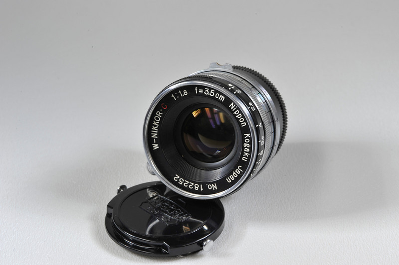35mm f1.8 W-Nikkor C with cap. incorrect rear cap. Condition is mint minus. Chrome. Includes original box, case and instructions with hang tags.