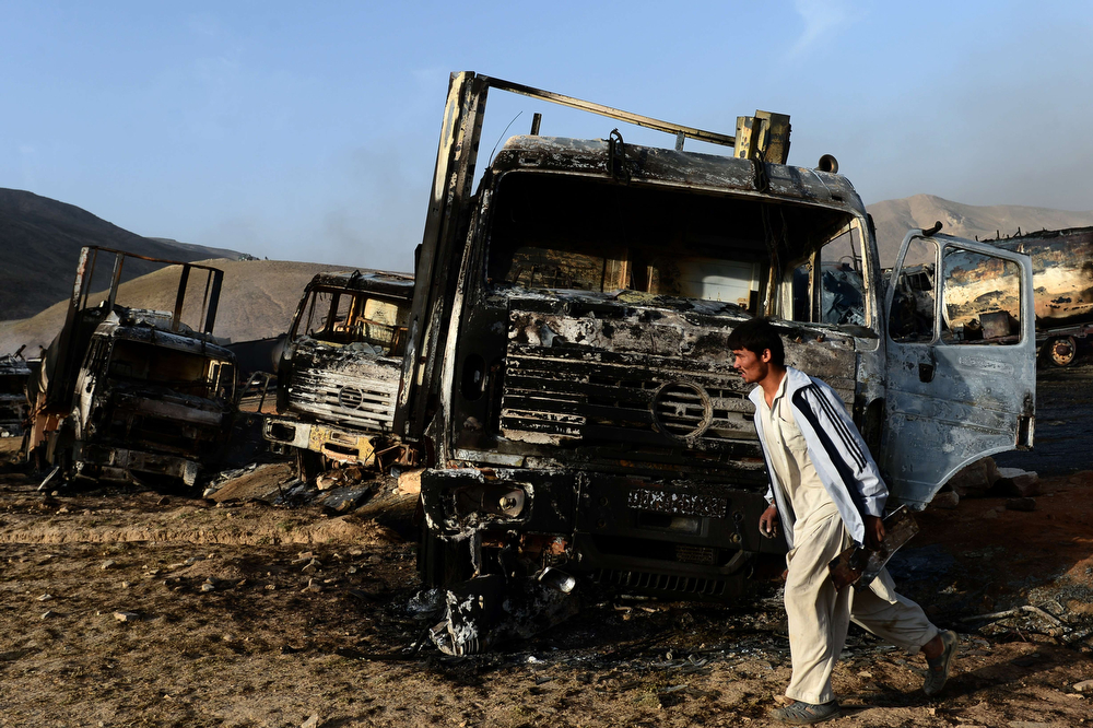 . An Afghan resident walks past burned-out fuel trucks following an overnight attack by Taliban militants in Chawk-e-Arghandi on outskirts of Kabul on July 5, 2014. Taliban militants set fire to dozens of fuel trucks on the outskirt of Kabul, officials said.The fire triggered by a sticky bomb set a blaze dozens of fuel tankers waiting to enter the city in Chawk-e-Arghandi parking lot west of Afghan capital over night. (WAKIL KOHSAR/AFP/Getty Images)